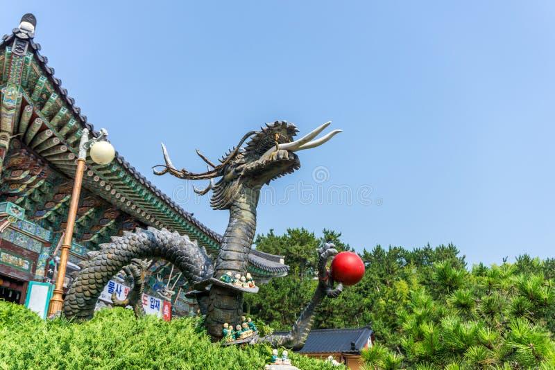 Metal sculpture of Chinese dragon holding red ball at Haedong Yonggungsa Temple. BUSAN, SOUTH KOREA - JULY 20, 2017 : Metal sculpture of Chinese dragon holding royalty free stock images