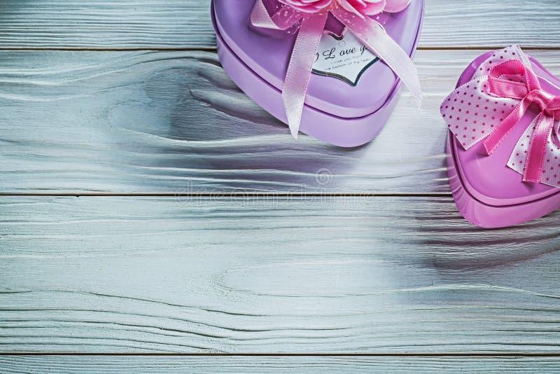 Metal sercowata mała teraźniejszość boksuje z różowymi faborkami na drewnie fotografia stock