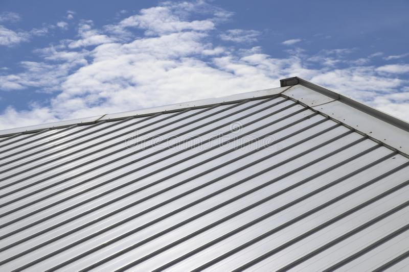 Metal sheet roof and slope with clouds and blue sky royalty free stock images