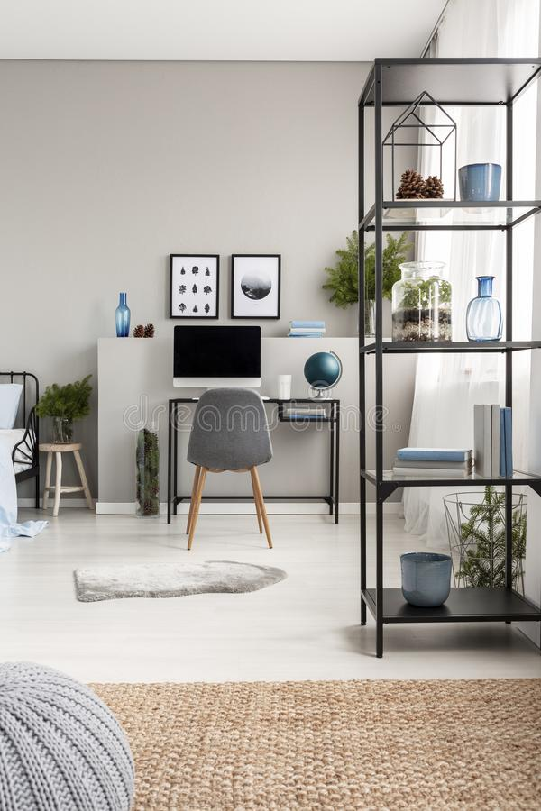 Metal shelf with cones, vases, plant and books in grey scandinavian home office with industrial desk with computer and copy space stock photography