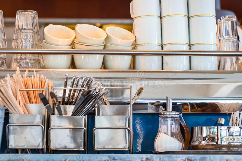Metal shelves with coffee utensils dishware, sugar pot, and glasses stock photo
