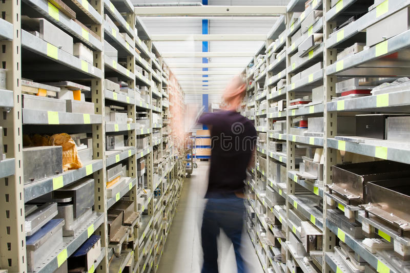 Metal shelves and technician at plant. Metal Shelves With Spare Parts And Technician In Plant Interior stock images