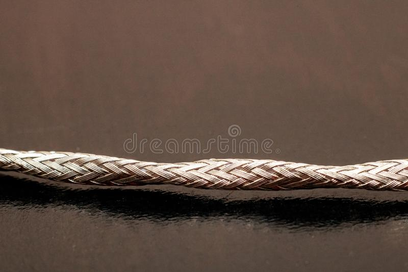 Metal shielded wire on black background close up stock photography