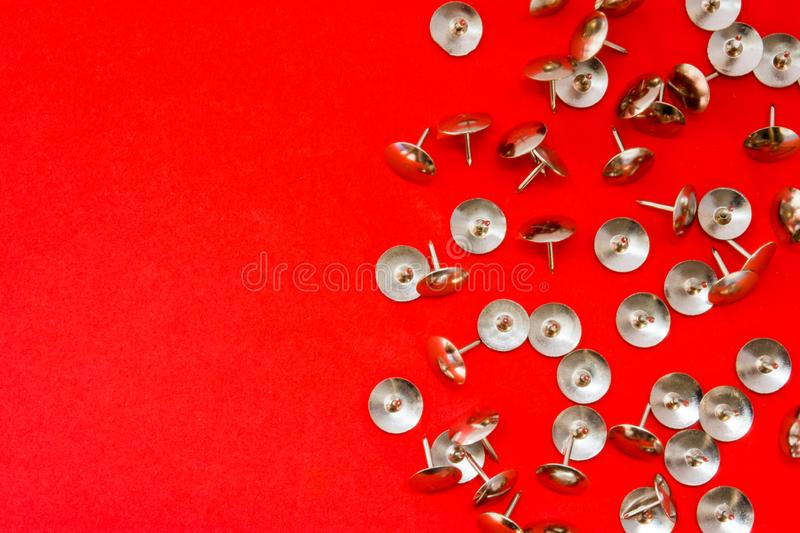 Metal shiny sharp pins or thumbtracks scattered on red background with clean area of photo for labels or headers. Symbol of sympto royalty free stock photos