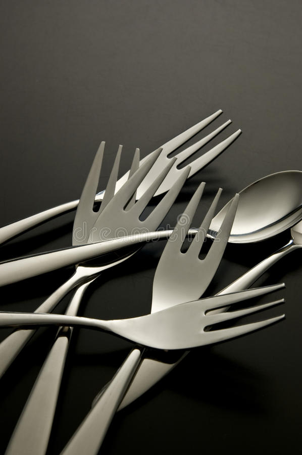 The metal shiny spoon and fork on black background