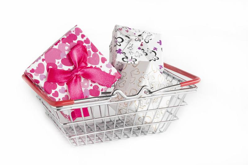 Metal shopping basket full of isolated gifts on a white background stock images