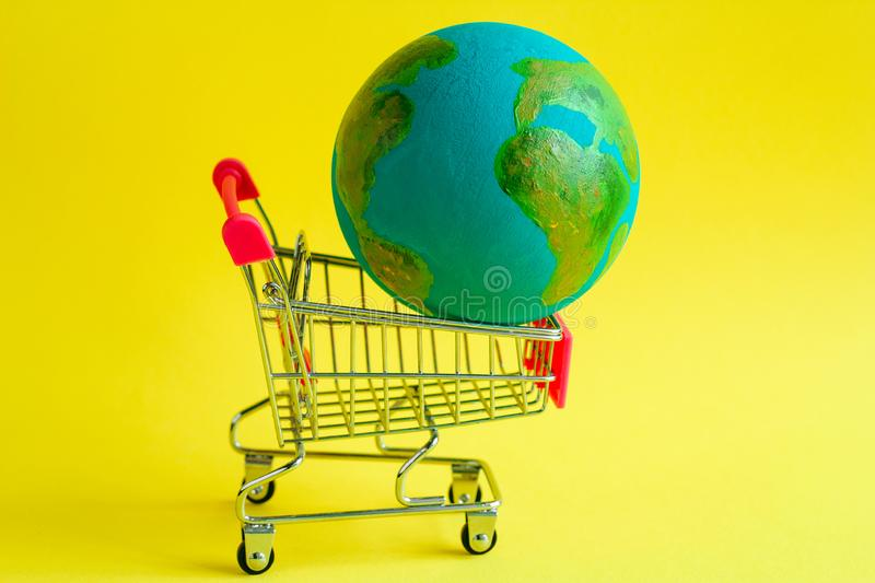 Shopping cart with a model of the planet Earth inside on a yellow background. Metal shopping cart with a model of the planet Earth inside on a yellow background stock photo