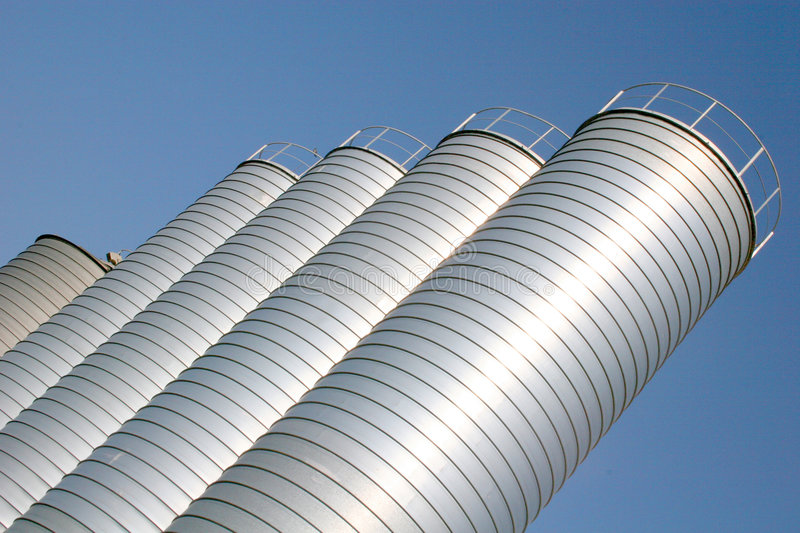 Metal Silos. Tall metal silos for storing grain against a blue sky royalty free stock photography