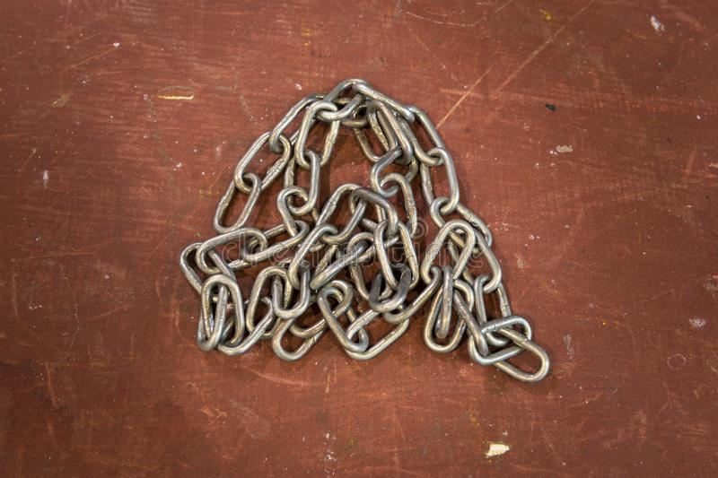 Metal silver chain against rough and scratched red background, surface. Industrial wallpaper. royalty free stock images