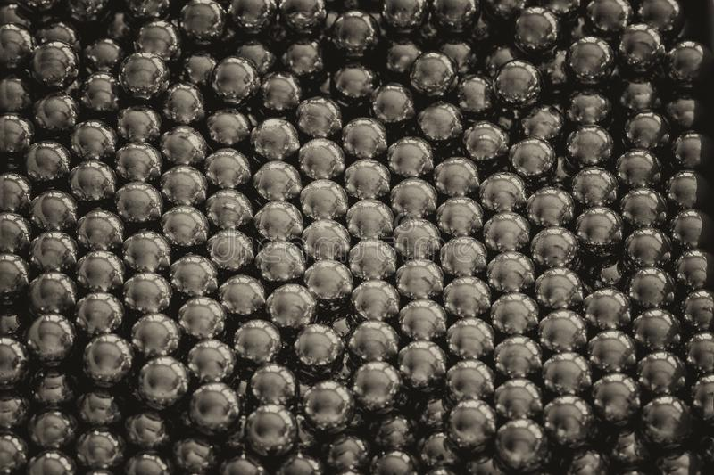 Metal sling balls arranged in rows, balls for bearings. Close-up and perspective with the blurring of many objects forming an ordered structure. Metal shiny stock photography