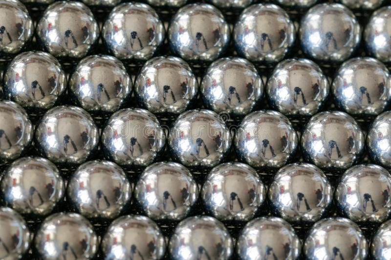 Metal sling balls arranged in rows, balls for bearings. Close-up and perspective with the blurring of many objects forming an ordered structure. Metal shiny royalty free stock photography