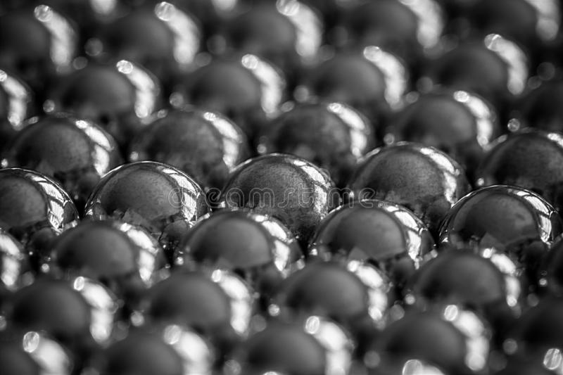 Metal sling balls arranged in rows, balls for bearings. Close-up and perspective with the blurring of many objects forming an ordered structure. Metal shiny royalty free stock image