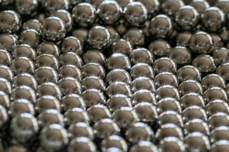 Metal sling balls arranged in rows, balls for bearings. Close-up and perspective with the blurring of many objects forming an ordered structure. Metal shiny royalty free stock photos