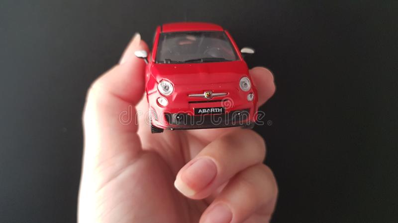 Metal small Fiat 500 model in female hand royalty free stock image