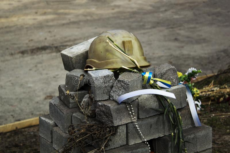 Metal soldiers helmet lying on pile of concrete grey bricks. Soldiers Military Ammunition stock image