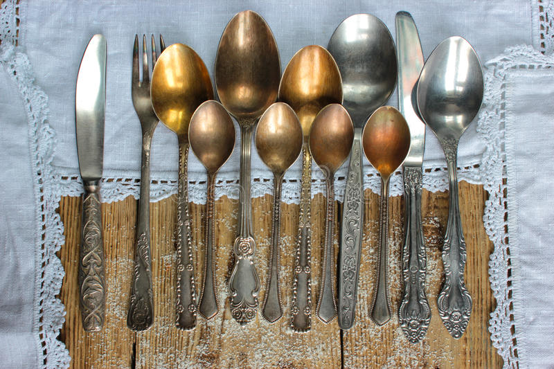 Metal spoons, forks, knives, on an old rustic table. Like a frame used a tablecloth crocheted stock photos