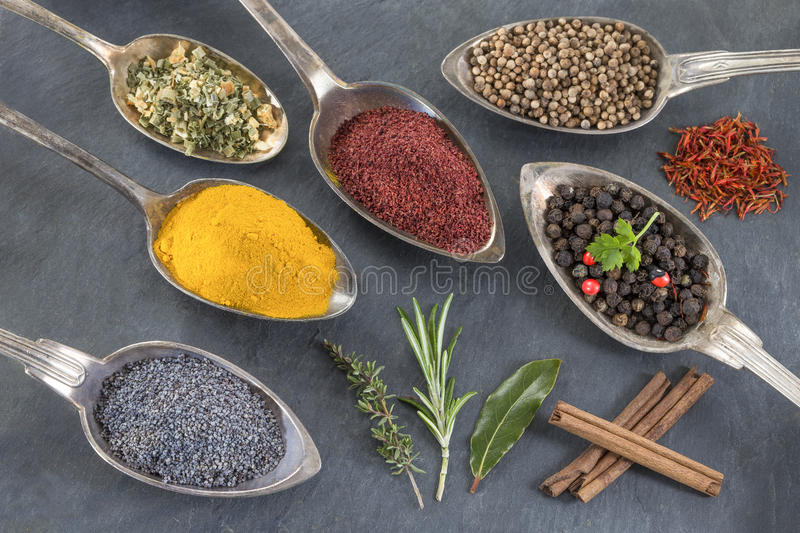 Metal spoons with various ground spices on slate background royalty free stock photos