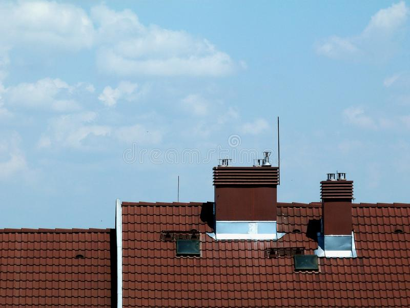 Metal stacks and chimneys on brown clay or concrete tile roof stock photography