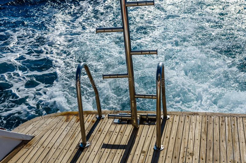 Metal staircase for descent into the water and wave trace with white foam on a water surface behind of fast moving yacht stock photography