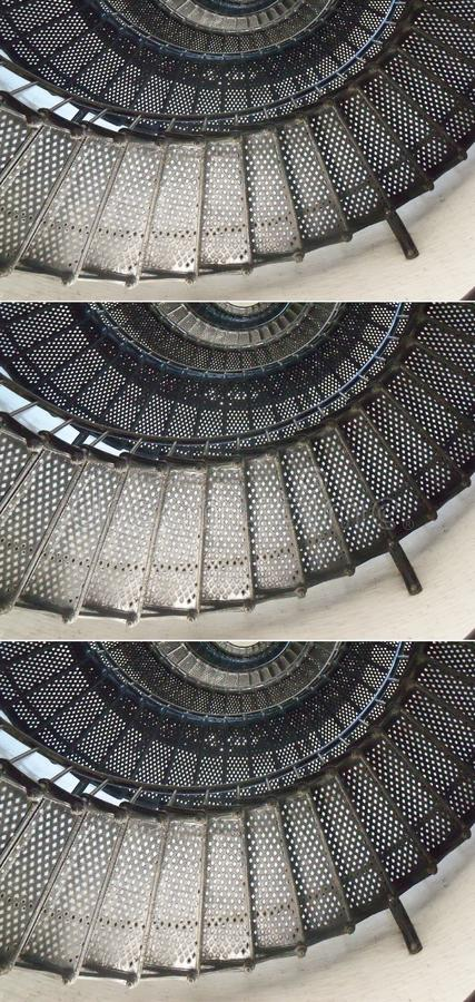 A metal staircase winds upwards in three photos stacked together. A black metal staircase winds upward as far as the eye can see in three photos stacked together royalty free stock images