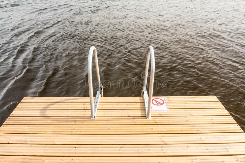 Metal stairs of a wooden pier into lake water at autumn sunny day.  stock images