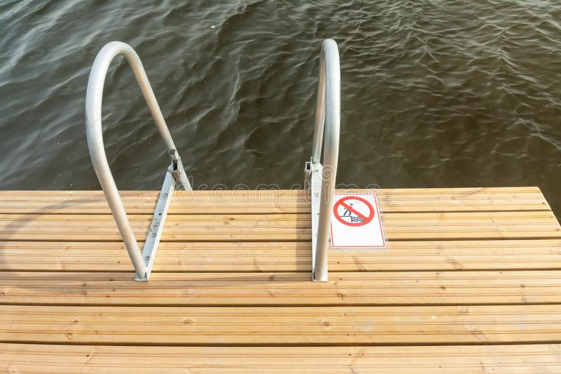 Metal stairs of a wooden pier into lake water at autumn sunny day.  stock image