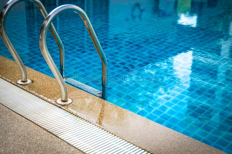 Metal steel handle at edge poolside of swimming pool in hotel stock photography