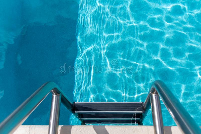 Metal steps in the pool, swimming pool equipment royalty free stock photos