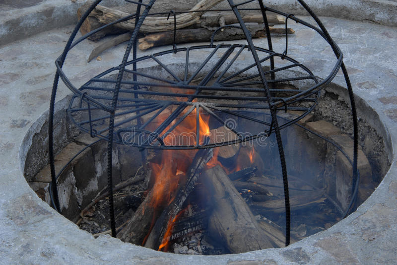 Metal structure smokehouse. In the pit a construction of metal rods for smoke. metal structure for cooking on fire royalty free stock image