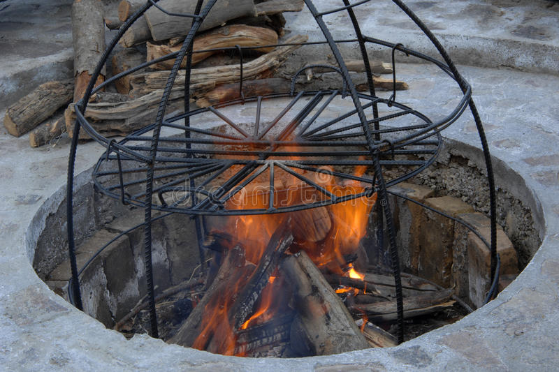 Metal structure smokehouse. In the pit a construction of metal rods for smoke. metal structure for cooking on fire royalty free stock photo