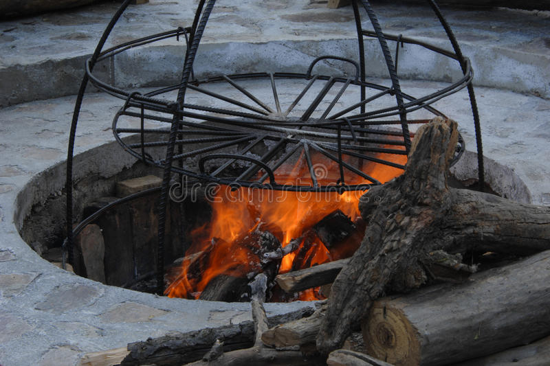 Metal structure smokehouse. In the pit a construction of metal rods for smoke. metal structure for cooking on fire royalty free stock photography