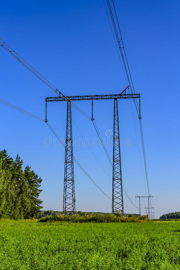 Metal supports and cables of a high-voltage transmission line over a green field in the early summer morning royalty free stock images