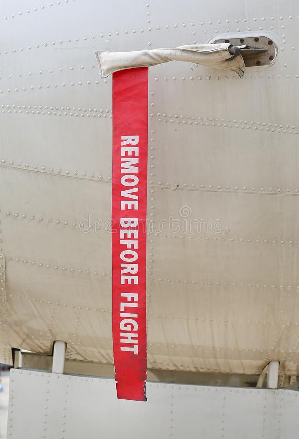 Metal surface of military aircraft with red ribbon warning caution `REMOVE BEFORE FLIGHT`.  stock photos