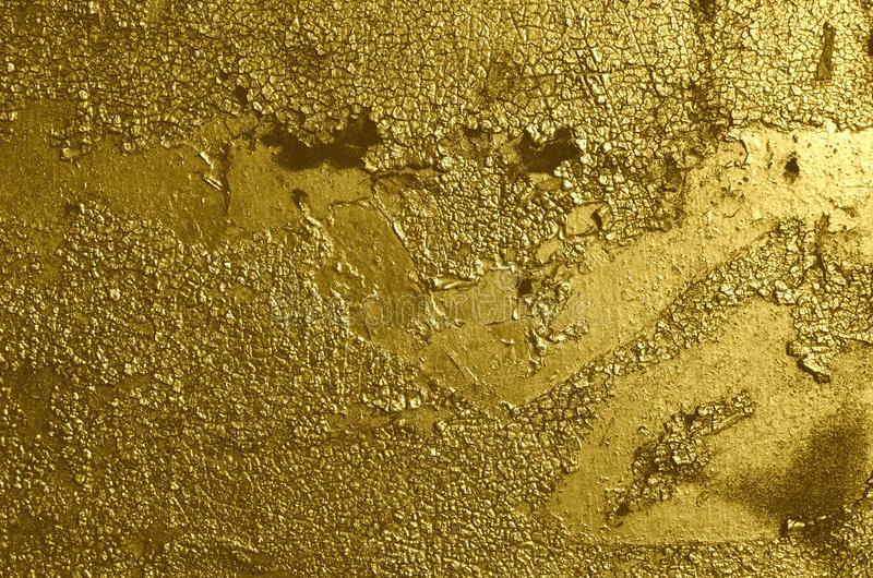 Old weathered cracked peeling airbrushed golden graffiti paint. Metal surface sprayed with graffiti paint of golden color. Rough texture of the old weathered royalty free stock image