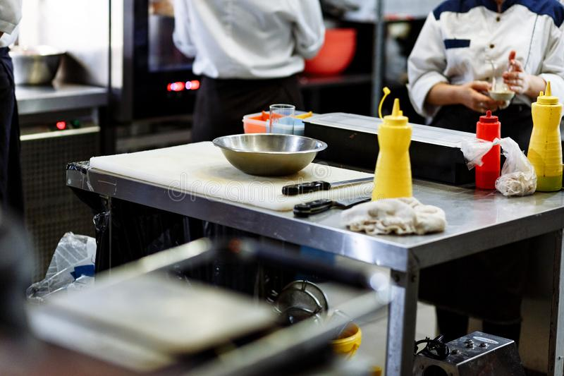 Metal table and a backs of cooks in the restaurant kitchen royalty free stock image