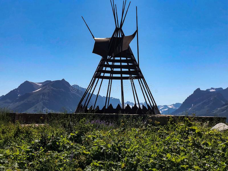 Metal tepee with mountain landscape at Glacier National Park. This metal tepee stands proudly with massive snowy mountains in the background at Glacier National stock images