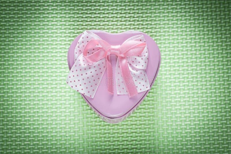 Metal teraźniejszości różowy sercowaty pudełko z łękiem na zielonym tle fotografia stock