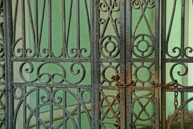 Metal texture of black and rusty steel bars with a forged pattern on the gate stock image