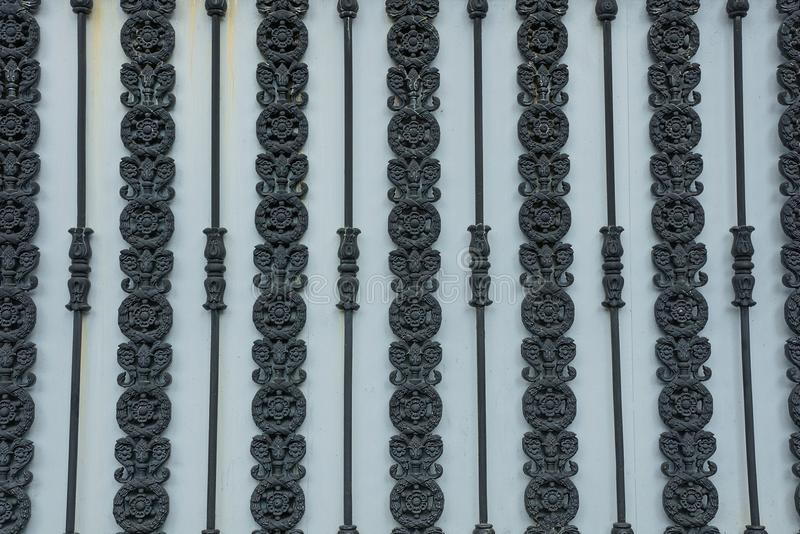 Metal texture of black wrought iron rods with a pattern on a gray fence royalty free stock photo