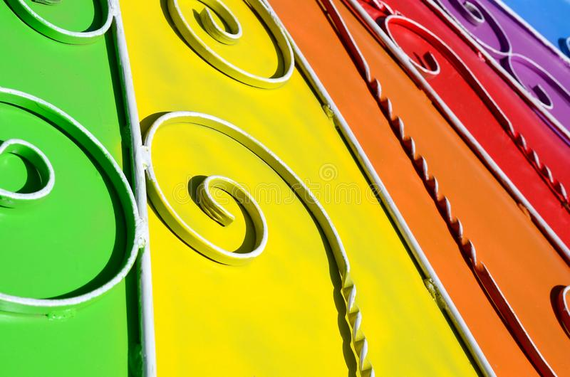 Metal texture of a piece of colored wall with a forged pattern. Rainbow colors stock images