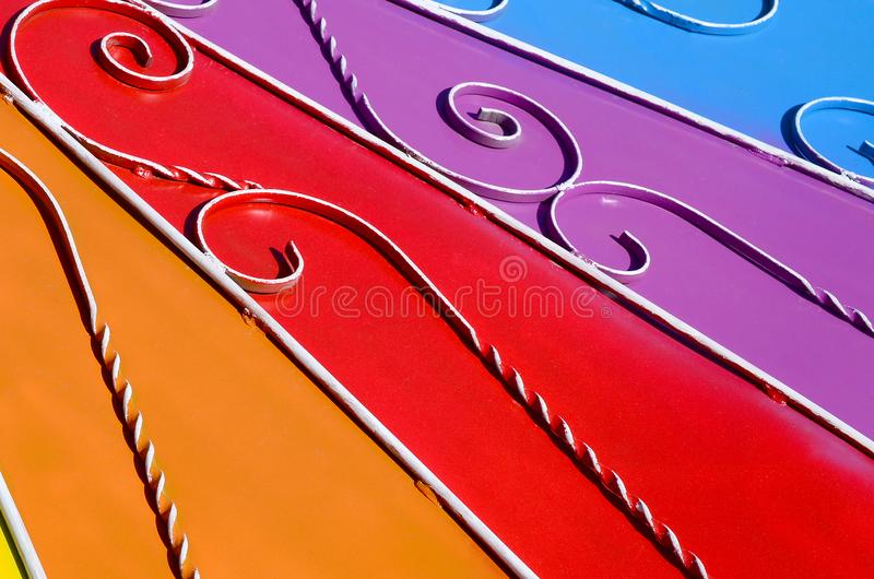 Metal texture of a piece of colored wall with a forged pattern. Rainbow colors stock image
