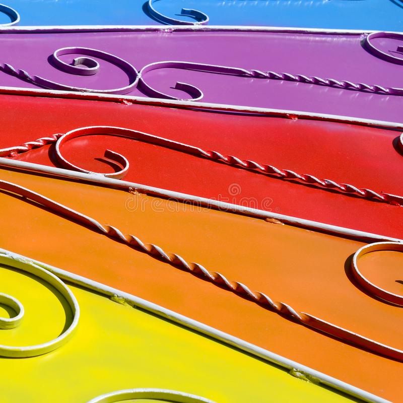 Metal texture of a piece of colored wall with a forged pattern. Rainbow colors royalty free stock photography