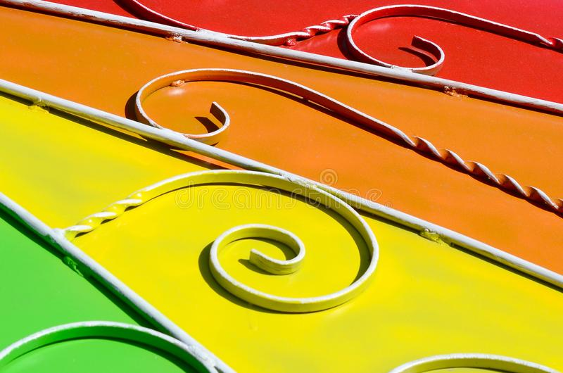 Metal texture of a piece of colored wall with a forged pattern. Rainbow colors stock photo