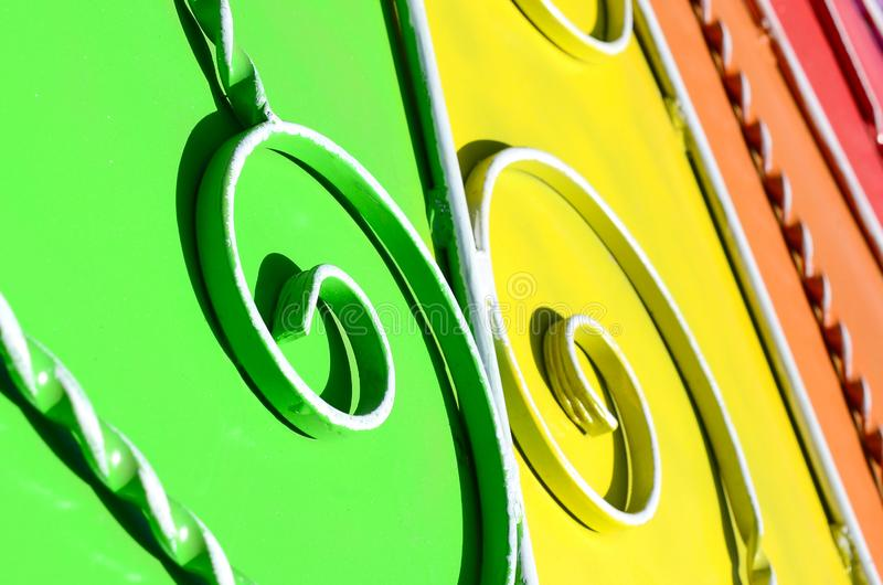 Metal texture of a piece of colored wall with a forged pattern. Rainbow colors royalty free stock photos