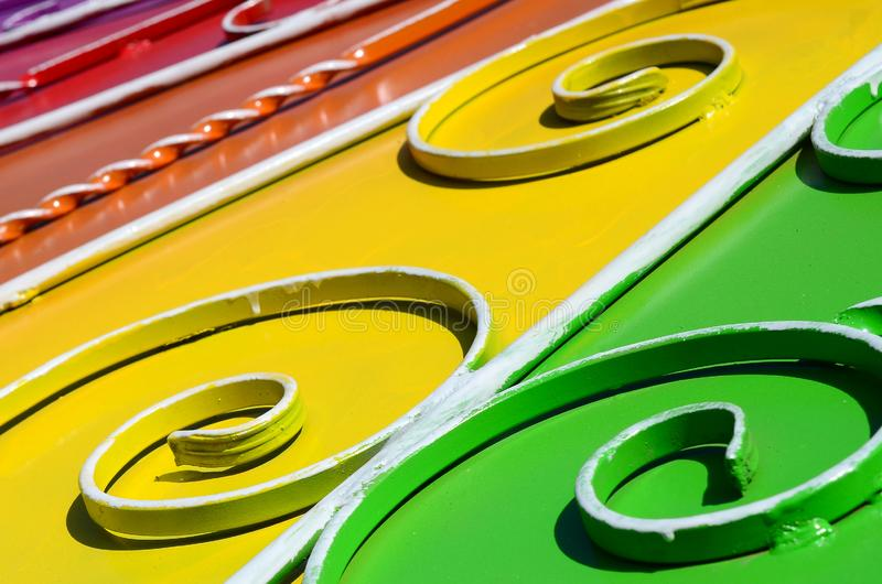 Metal texture of a piece of colored wall with a forged pattern. Rainbow colors royalty free stock images