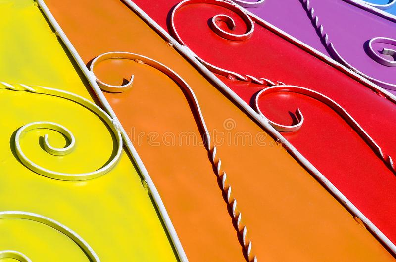 Metal texture of a piece of colored wall with a forged pattern. Rainbow colors royalty free stock photo