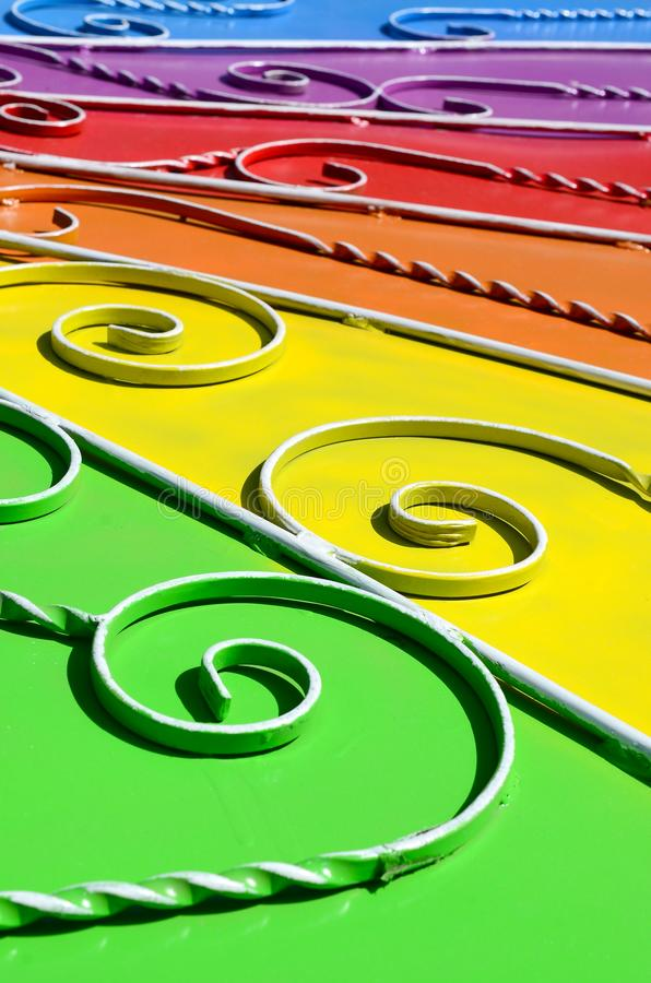 Metal texture of a piece of colored wall with a forged pattern. Rainbow colors stock photos