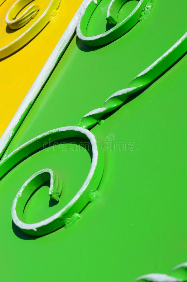 Metal texture of a piece of colored wall with a forged pattern. Rainbow colors stock photography
