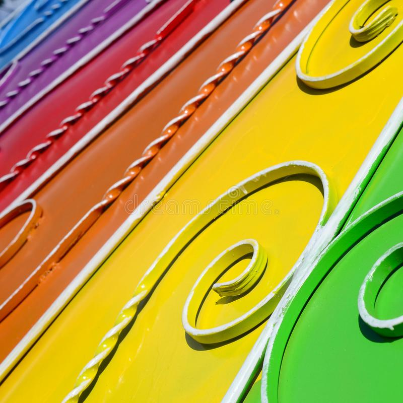 Metal texture of a piece of colored wall with a forged pattern. Rainbow colors royalty free stock image