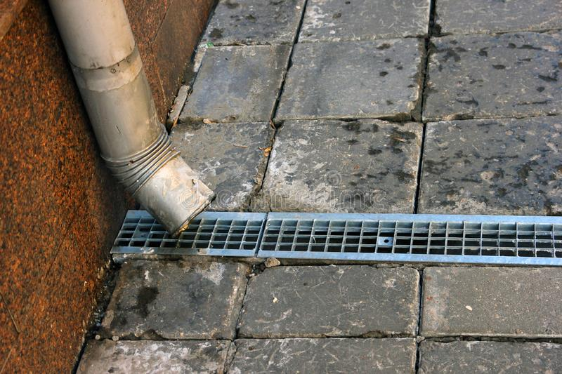 Metal tinplate downpipe and drain tray with grating closeup. Metal tinplate downpipe and drain tray with grating stock image